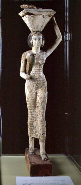 Female bearer of offerings carrying a water vase in her hand and a vessel on her head c.1950 BC